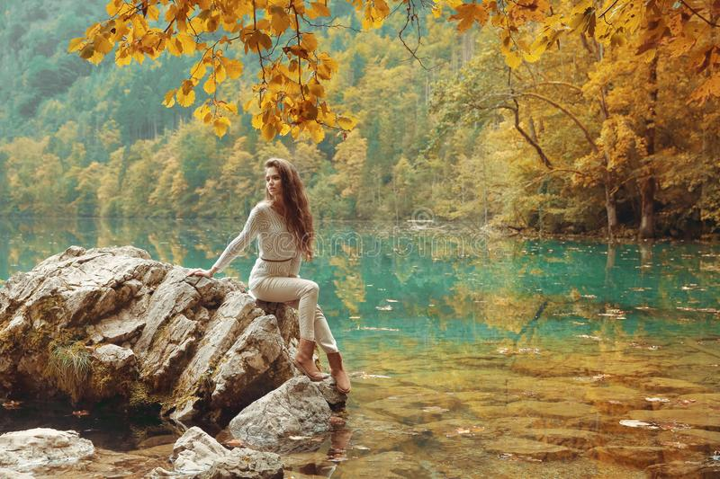 Yellow leaves over Obersee Lake autumn landscape. Beautiful tour. Ist woman on stone in crystal water in Berchtesgaden National Park, Salet am Koenigssee stock photos