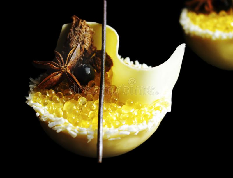 Yellow lemon jelly caviar and white melon mousse dessert with coconut, honey, white chocolate and star anise isolated on black stock photography