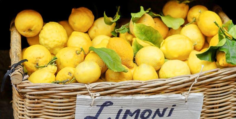 Yellow lemons in basket on market royalty free stock photos