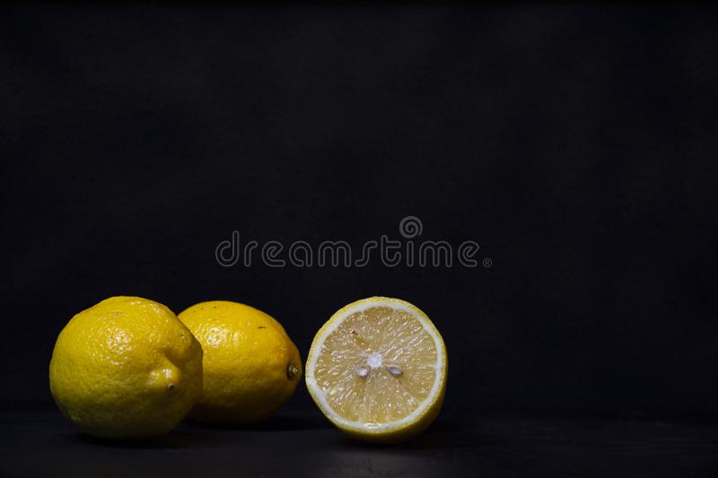 Yellow lemons on a black wooden background from biologic agriculture royalty free stock image