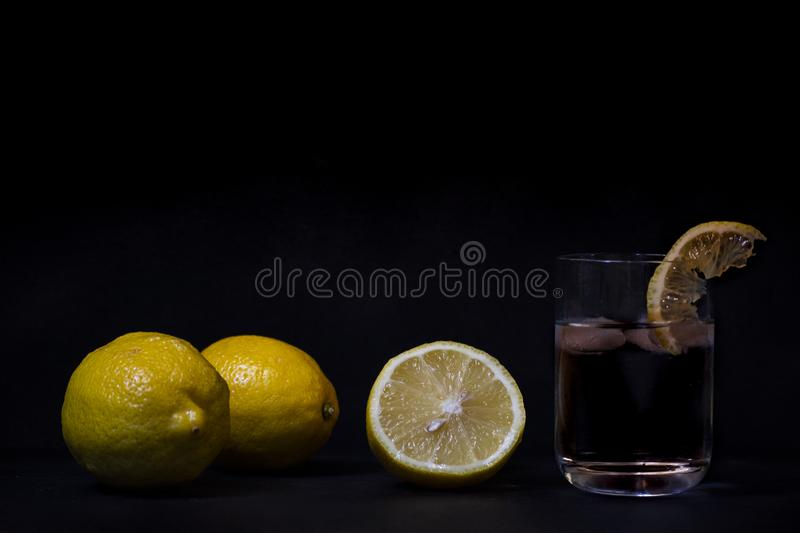 Yellow lemons on a black wooden background from biologic agriculture royalty free stock photo