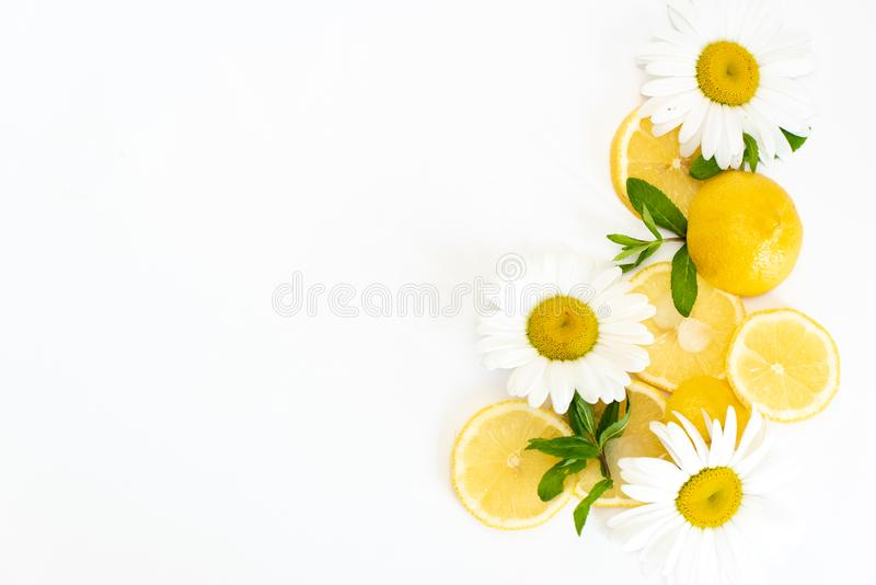 Yellow lemons with fresh chamomile flowers on white plate royalty free stock photo