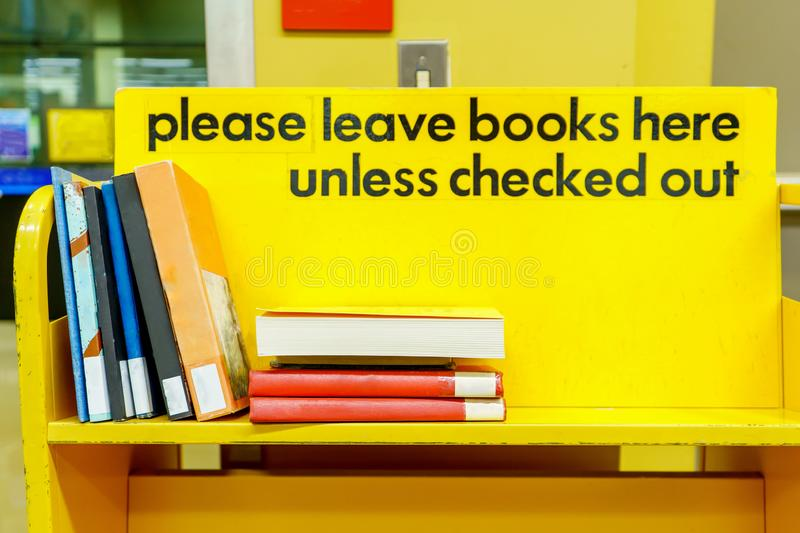 Yellow library book cart with sign, and books stacked on a shelf to be put away. Yellow library book cart with sign in black letters, and books stacked on a stock photography