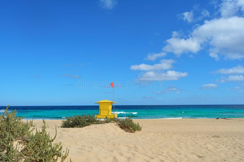 Yellow lifeguard post on the beach of Corralejo, Fuerteventura, Spain. Golden sands, cloudy blue sky and turquoise ocean royalty free stock image