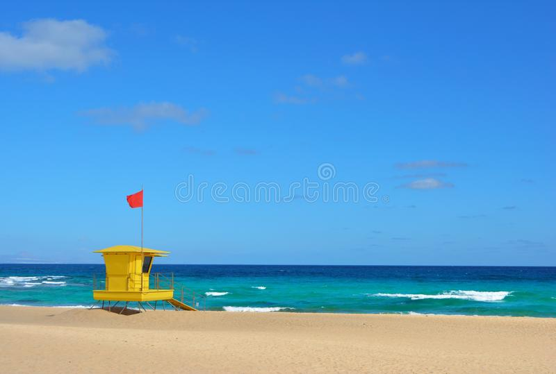 Yellow lifeguard post on the beach of Corralejo, Fuerteventura, Spain. Golden sands, cloudy blue sky and turquoise ocean stock photography
