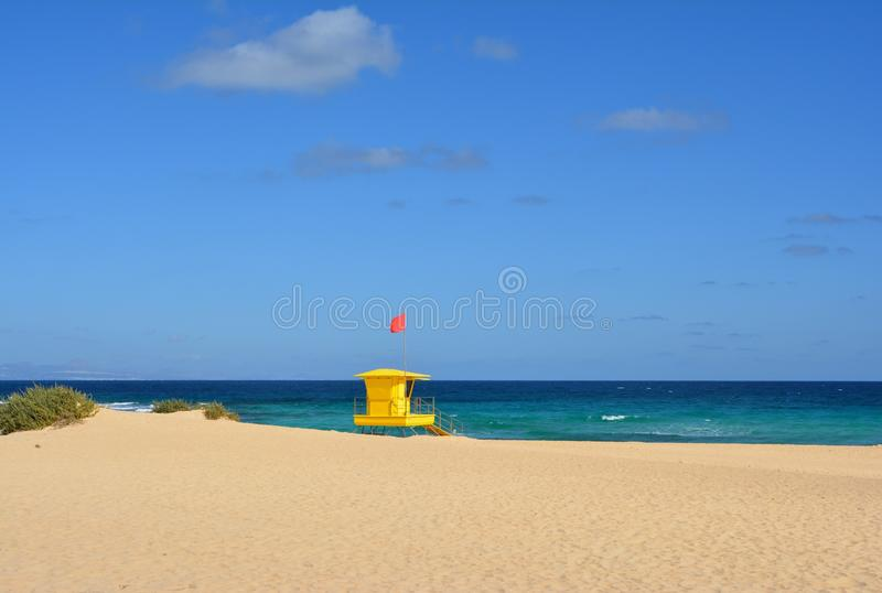 Yellow lifeguard post on the beach of Corralejo, Fuerteventura, Spain. Golden sands, cloudy blue sky and turquoise ocean royalty free stock photography