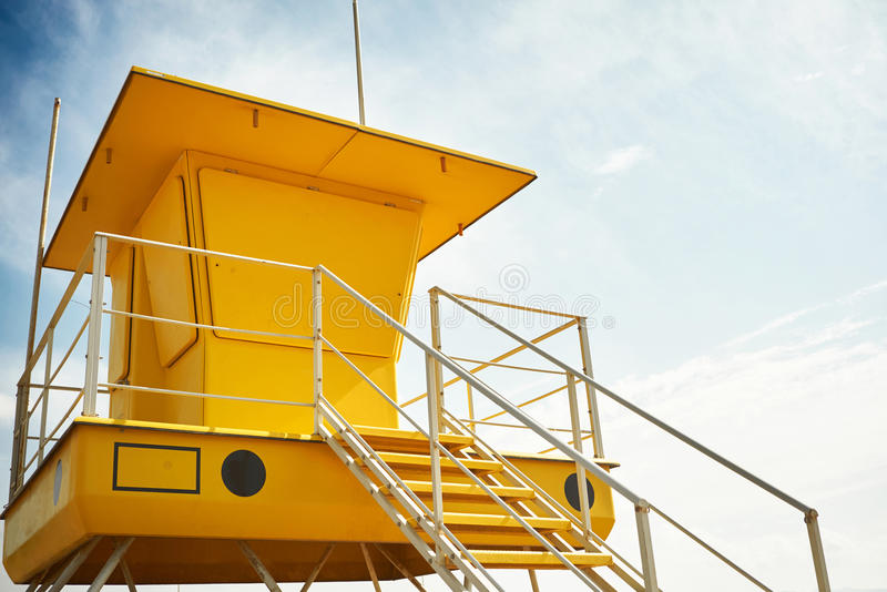 Yellow lifeguard post on an empty beach. Bright yellow lifeguard post with no lifeguards and windows bolted shut against sky background Commercial image royalty free stock photos