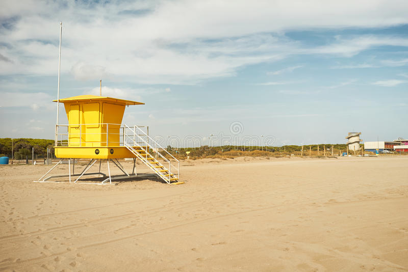 Yellow lifeguard post on an empty beach. Bright yellow lifeguard post and other distant beach structures on a quiet day with no people around stock image
