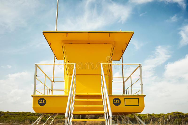 Yellow lifeguard post on an empty beach. Close up ground level shot of a closed yellow lifeguard post on the background of blue sky with some clouds royalty free stock image