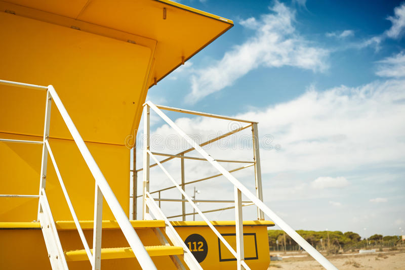 Yellow lifeguard post on an empty beach. Close up shot of a beautiful yellow lifeguard post against the background of blue sky and some white clouds royalty free stock photo