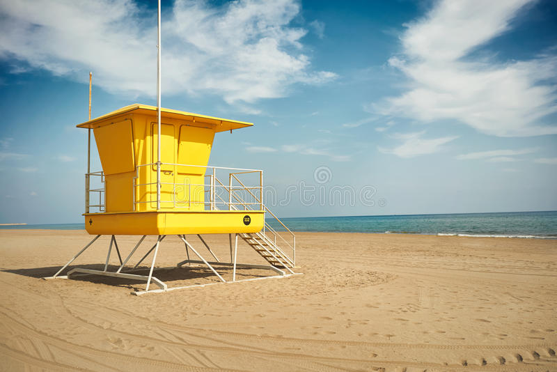 Yellow lifeguard post on an empty beach. Flowy white clouds above a sunlit yellow lifeguard post on an empty sandy beach near quiet sea stock photo