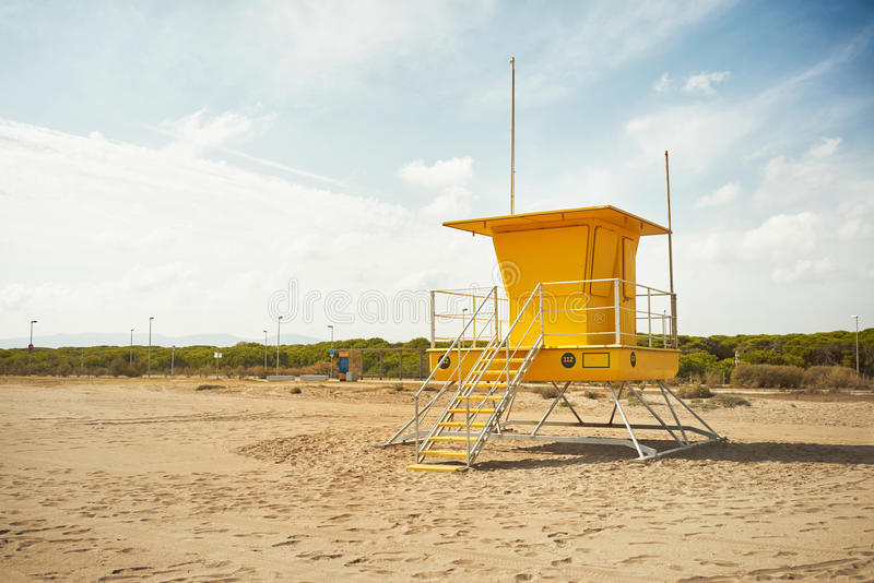 Yellow lifeguard post on an empty beach. Footprints on an empty beach around a bright yellow lifeguard post Commercial image royalty free stock photos