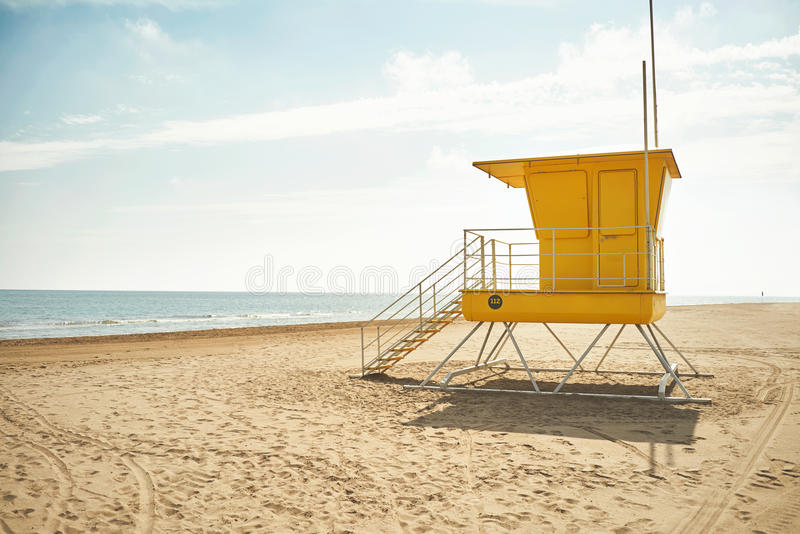Yellow lifeguard post on an empty beach. Yellow lifeguard post on an empty sandy beach with the background of blue sky with clouds and the sea royalty free stock photos