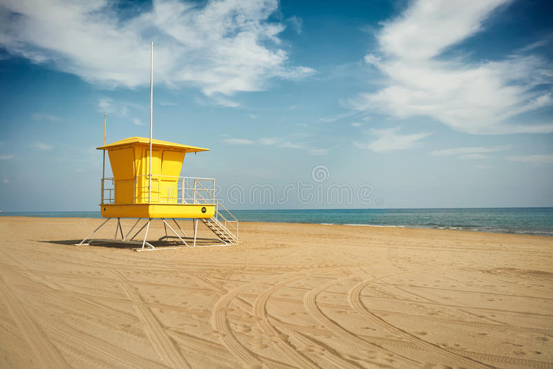 Yellow lifeguard post on an empty beach. Wheel tracks curving on the sand next to an empty lifeguard post on an empty beach under dramatic blue sky with white stock images