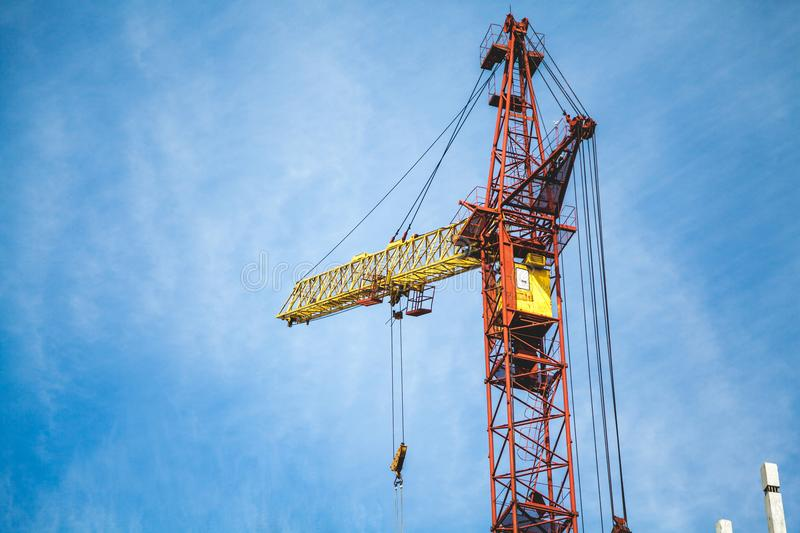 Lifting tower crane against cloudy sky background. Yellow lifting tower crane against a cloudy sky background view from below stock images