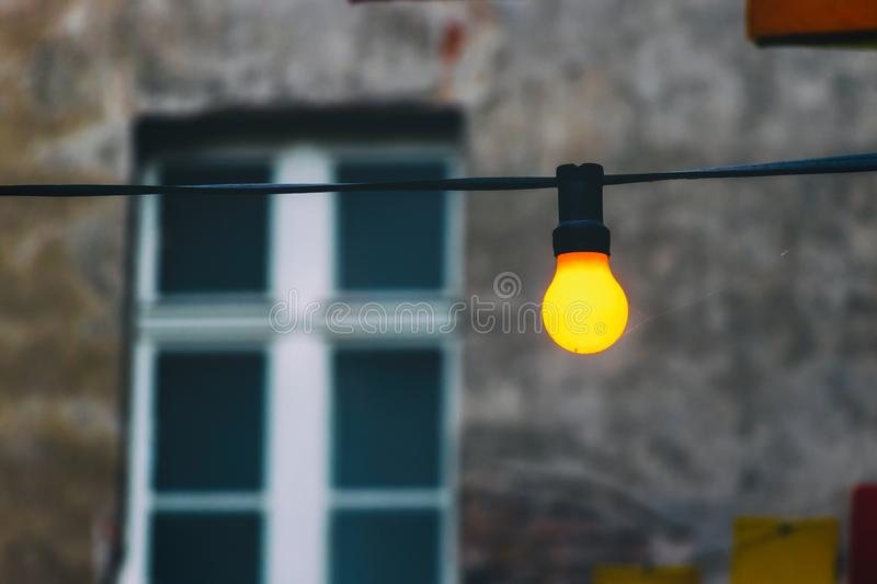 Yellow light bulb on the background of the old wall and window. stock photo