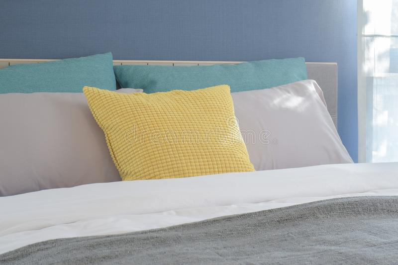 Yellow, light gray and green pillows setting on bed in modern interior bedroom stock photography