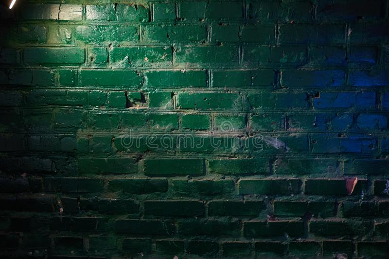 Yellow light of a lantern and blue flare on a brick wall stock photo