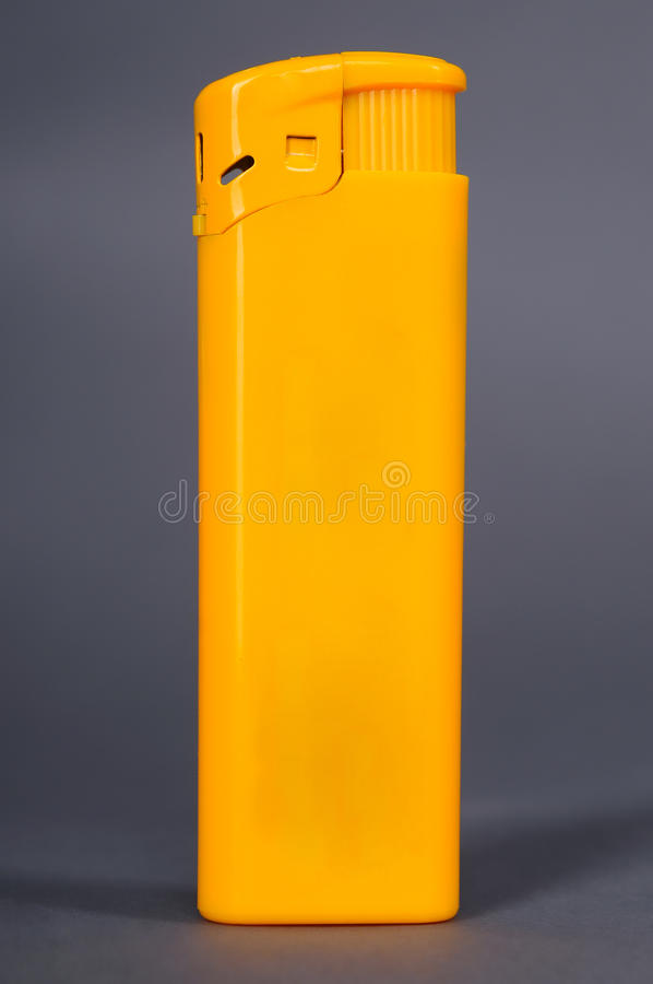 Yellow lighter on a gray background stock images