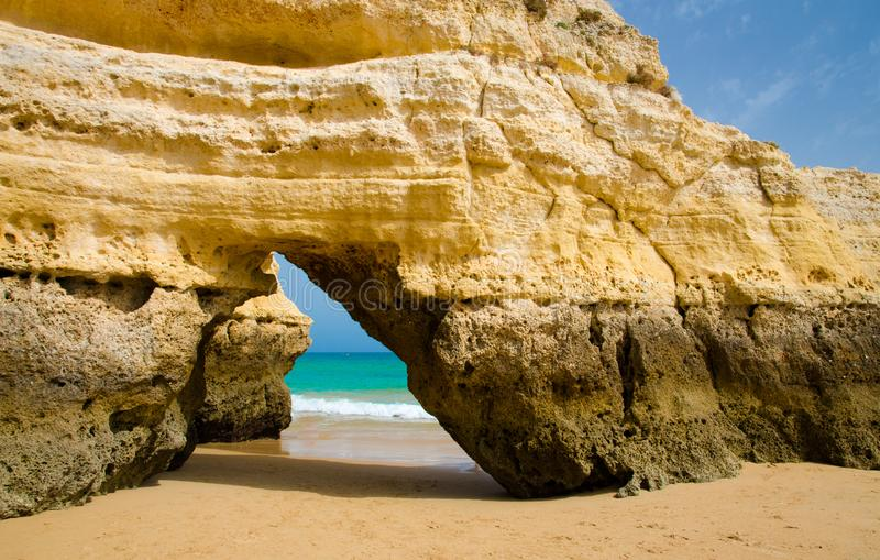 Yellow limestone arch on gold sandy beach, Portimao town, Portugal royalty free stock image