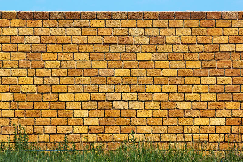 Yellow limestone brick wall with green grass and blue sky.  royalty free stock photos