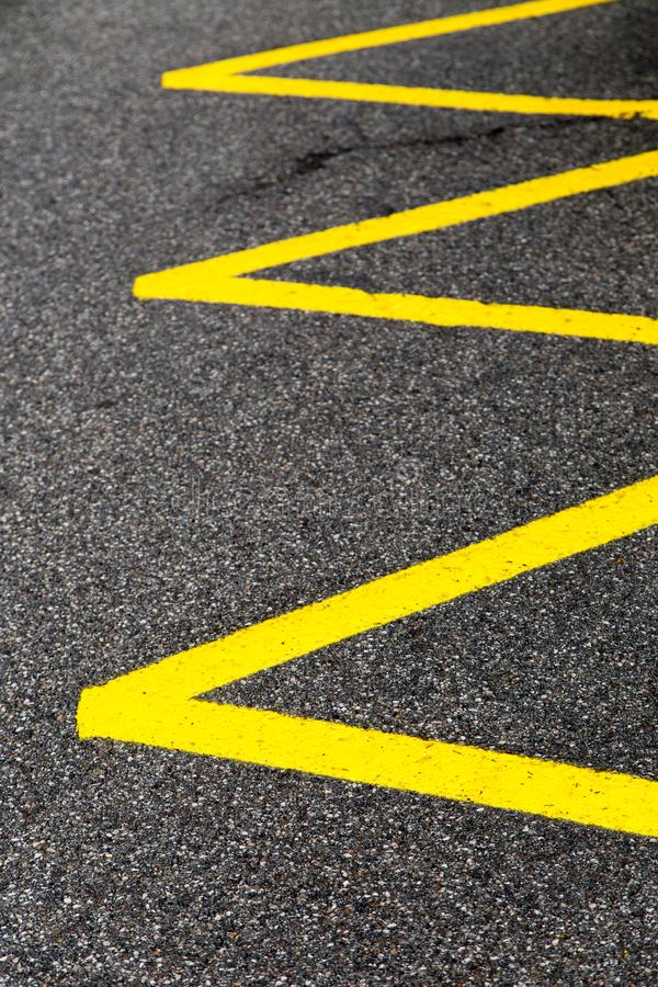 Yellow lines on tarmac pavement, no-parking zone. Yellow lines on dark tarmac pavement, no-parking zone royalty free stock photos