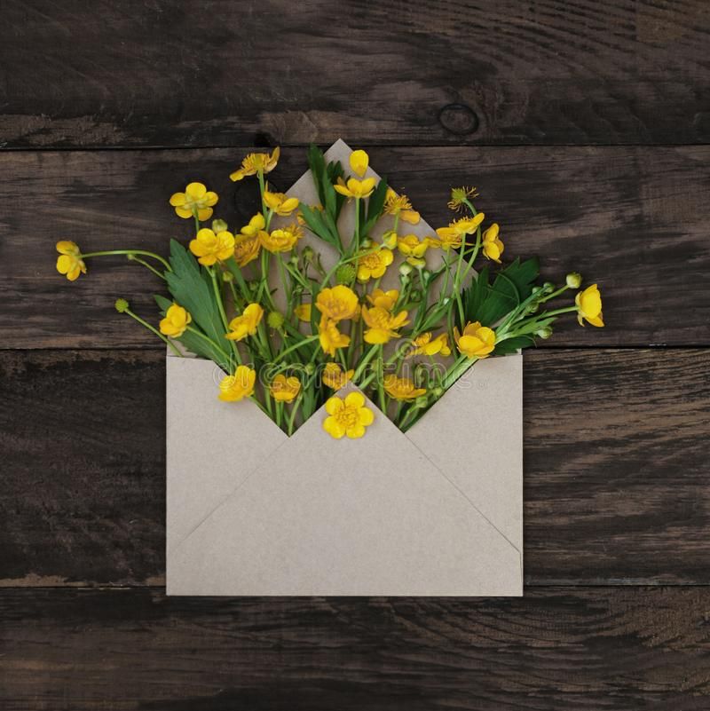 Yellow Little Flowers in Envelope Rustic Wooden Background Banner Flat Lay. Yellow Little Flowers in Envelope Rustic Wooden Background Banner royalty free stock image
