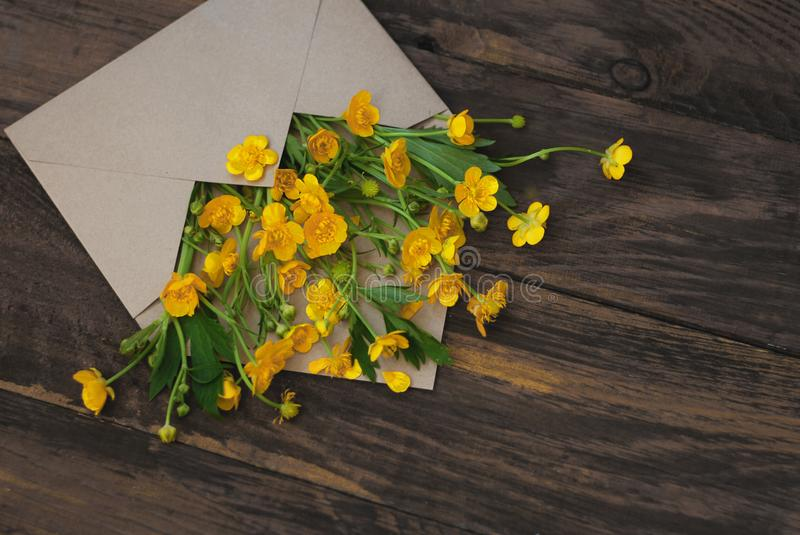 Yellow Little Flowers in Envelope Rustic Wooden Background Banner Flat Lay. Yellow Little Flowers in Envelope Rustic Wooden Background Banner royalty free stock images