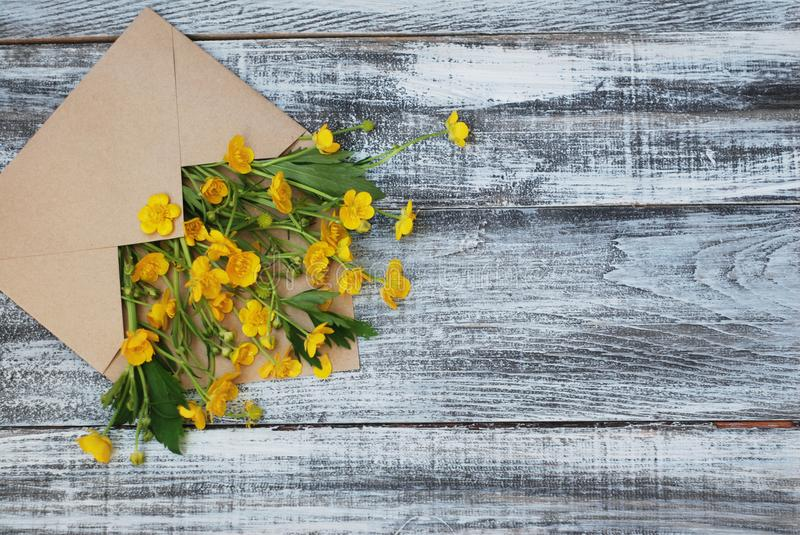 Yellow Little Flowers in Envelope Rustic Wooden Background Flat Lay. Yellow Little Flowers in Envelope Rustic Wooden Background stock images