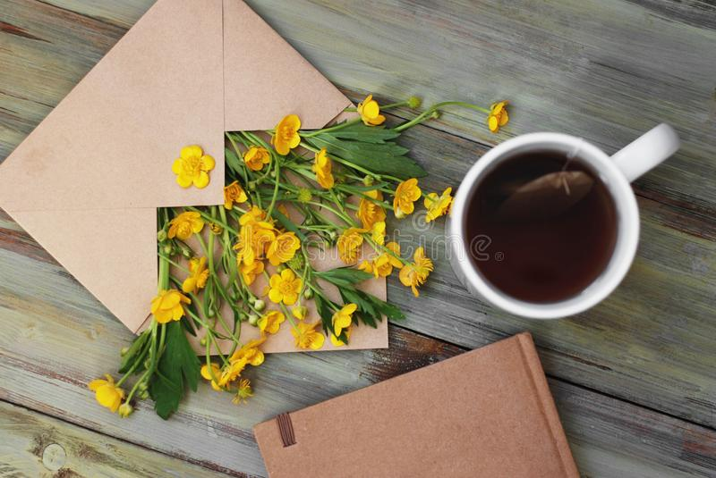 Yellow Little Flowers Tea Cup Notebook Envelope Rustic Wooden Background Flat Lay. Yellow Little Flowers Tea Cup Notebook Envelope Rustic Wooden Background stock photo