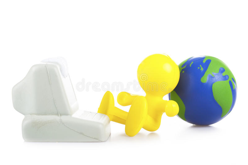 Yellow little man sits near the computer. Leaning a back on the Globe royalty free stock image
