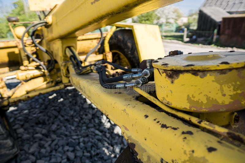 Yellow loader with empty bucket stands on a stone gravel during road construction works. The stones for the road stock image