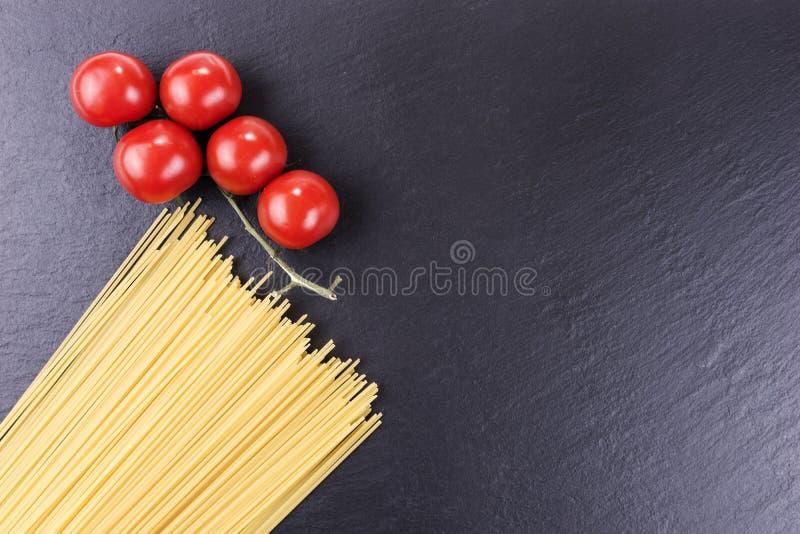 Yellow raw spaghetti and cherry tomatoes on black slate plate. Yellow long raw spaghetti and cherry tomatoes on black slate plate stock images