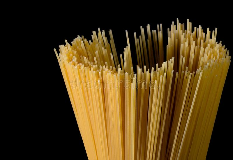Yellow long spaghetti on black background. Thin pasta arranged in rows. Yellow italian pasta. Long spaghetti. Raw spaghetti. Bolognese. Raw spaghetti wallpaper royalty free stock images