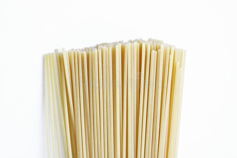 Yellow long spaghetti on a light background. Thin pasta arranged in rows. Italian raw pasta. Food background royalty free stock photography