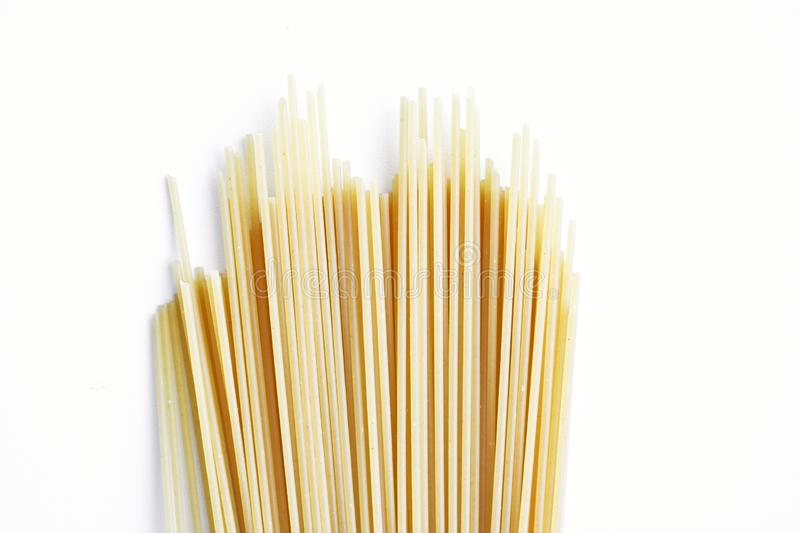 Yellow long spaghetti on a light background. Thin pasta arranged in rows. Italian raw pasta. Food background royalty free stock photo