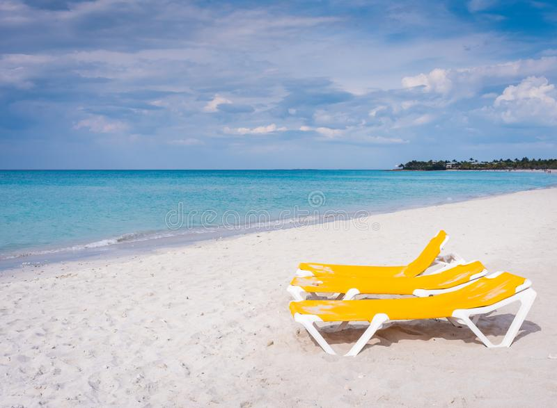 Yellow Lounges By The Blue Ocean. Bright yellow lounge chairs on white sand beach next to clear ocean in Varadero, Cuba royalty free stock images