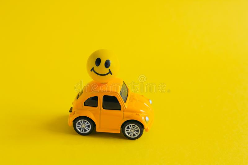 Machine with ball with painted smiling face attached to the roof on a yellow background, delivering a good mood concept. Yellow machine with ball with painted stock images