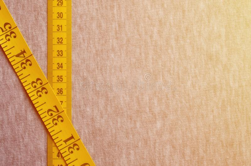 Yellow measuring tape with numerical indicators in the form of centimeters or inches lies on a gray knitted fabric. Concept indus. Try associated with sewing stock photos