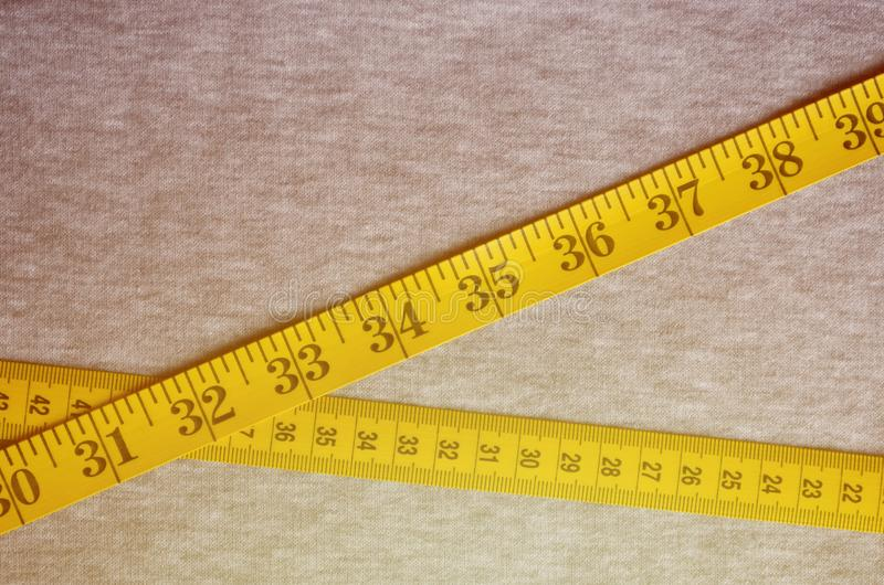 Yellow measuring tape with numerical indicators in the form of centimeters or inches lies on a gray knitted fabric. Concept indus. Try associated with sewing royalty free stock images