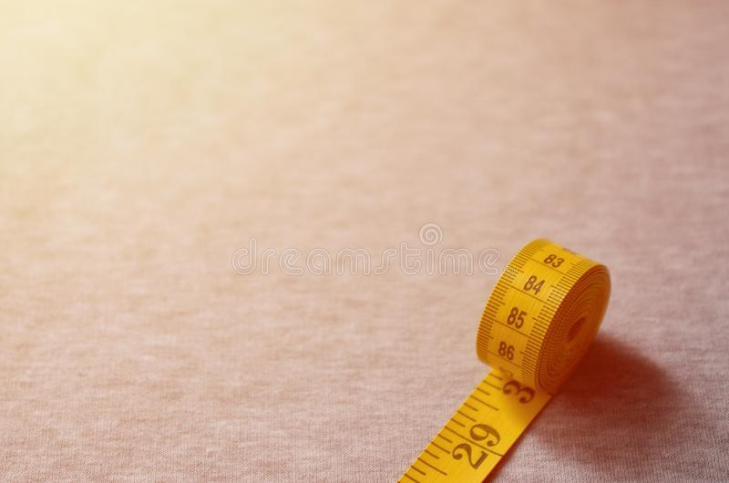 Yellow measuring tape with numerical indicators in the form of centimeters or inches lies on a gray knitted fabric. Concept indus. Try associated with sewing royalty free stock photography