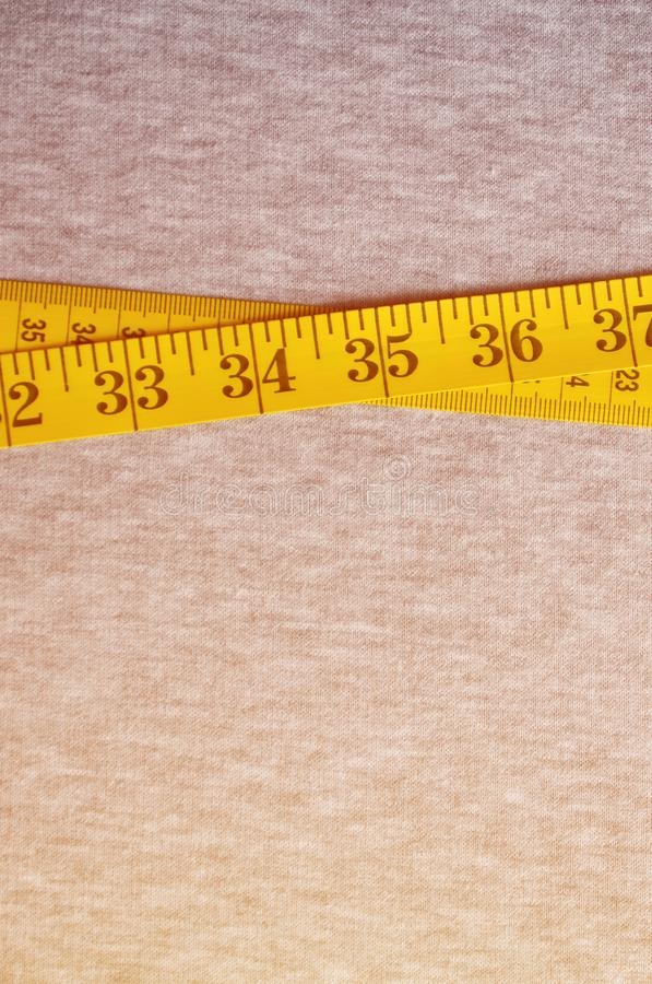 Yellow measuring tape with numerical indicators in the form of centimeters or inches lies on a gray knitted fabric. Concept indus. Try associated with sewing stock images