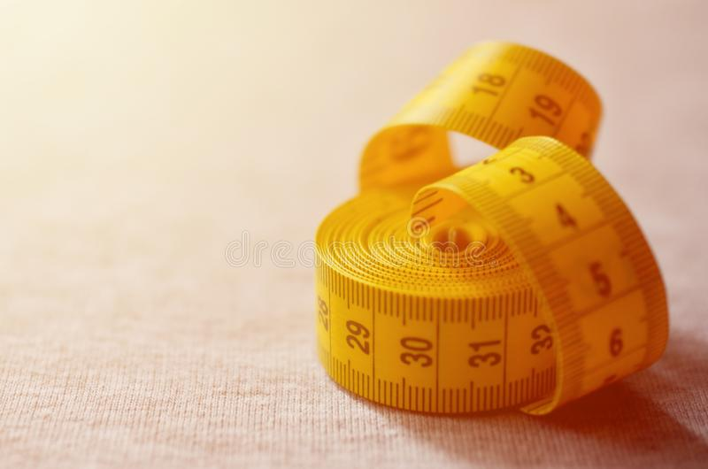 Yellow measuring tape with numerical indicators in the form of centimeters or inches lies on a gray knitted fabric. Concept indus. Try associated with sewing stock image