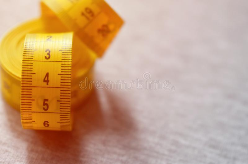 Yellow measuring tape with numerical indicators in the form of centimeters or inches lies on a gray knitted fabric. Concept indus. Try associated with sewing stock photo