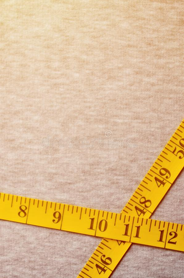 Yellow measuring tape with numerical indicators in the form of centimeters or inches lies on a gray knitted fabric. Concept indus. Try associated with sewing royalty free stock photo