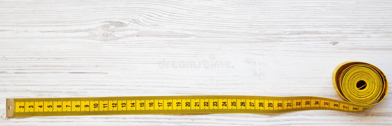 Yellow measuring tape on white wooden table, top view. From above, flat lay. stock photo