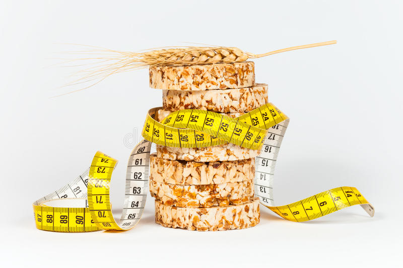 A yellow measuring tape wrapping sheaf of wheat and rice cakes. Healthy eating concept stock photos