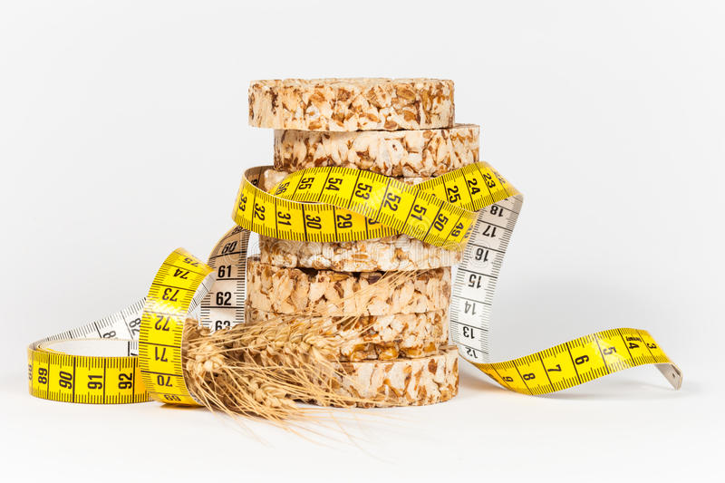 A yellow measuring tape wrapping sheaf of wheat and rice cakes. Healthy eating concept stock image
