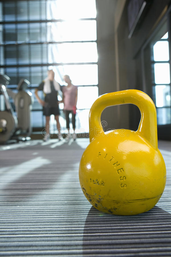 Yellow medicine ball on floor in health club with couple in background stock photo