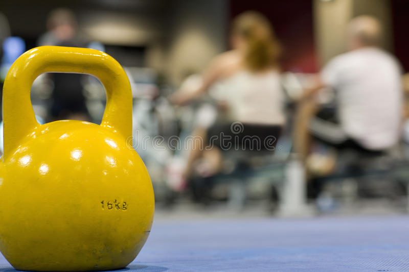 Yellow medicine ball in health club with people exercising in background royalty free stock image
